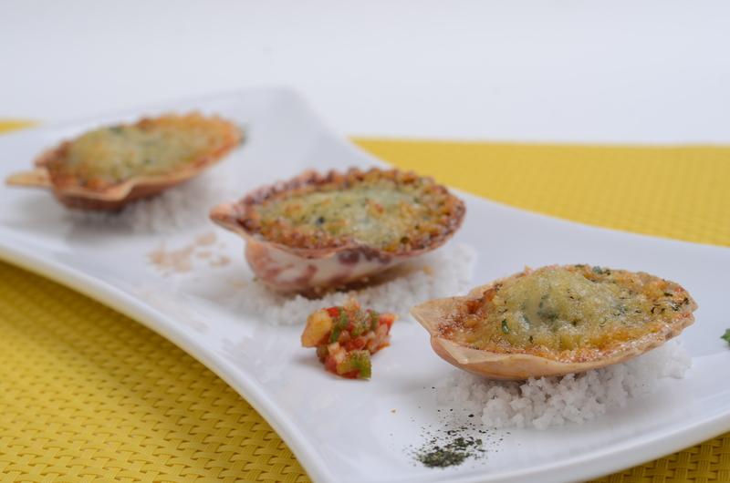 Vieiras con esencia de pimentón ahumado, gratinadas con escamas de queso y pan de hierbas